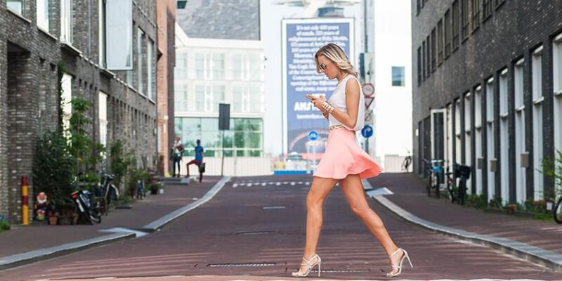 una ragazza cammina per strada col telefonino in mano