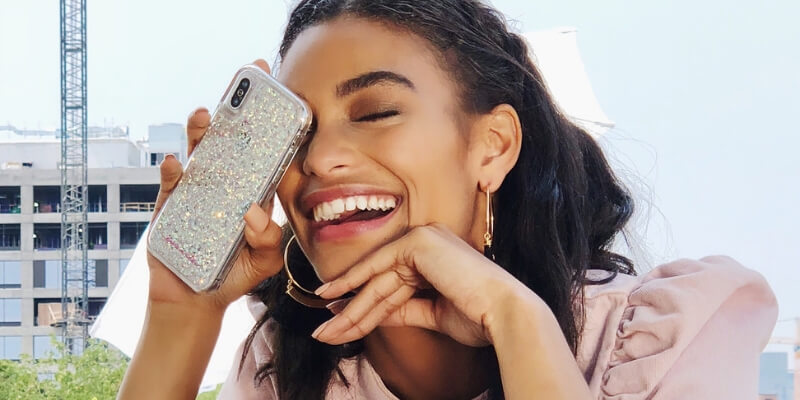 una ragazza ride sollevando l'iphone