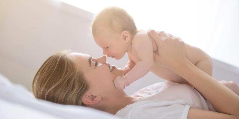 Un neonato gioca con la mamma