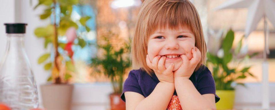 una bambina bionda sorride in primo piano
