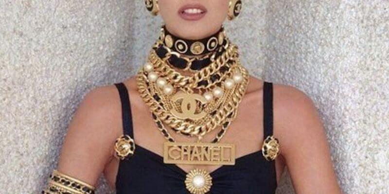 un dettaglio di linda evangelista che indossa vistosa bigiotteria con logo Chanel