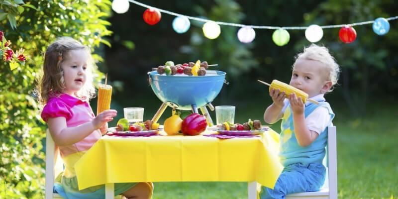due bambini mangiano pannocchie su un tavolino allestito all'aperto