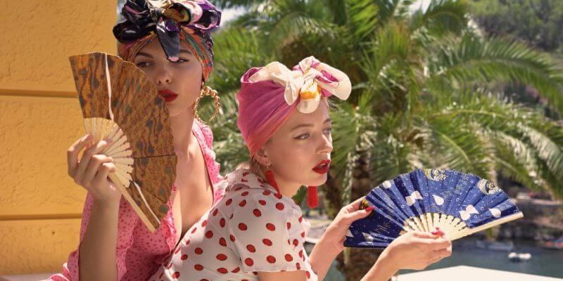 una foto con due ragazze che sfoggiano ventagli del marchio khukhu