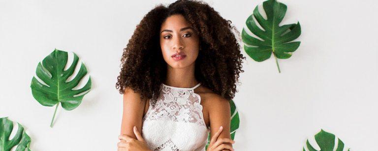 una ragazza di origini afro posa su uno sfondo di foglie verdi