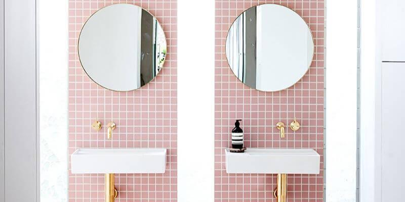 due lavandini gemelli su una parete di piastrelle rosa