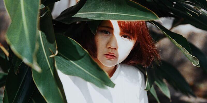 una ragazza orientale sbuca da dietro delle foglie
