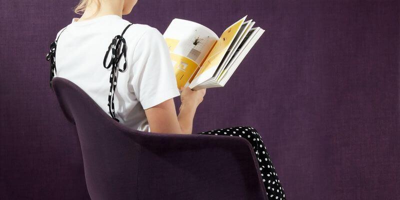 una ragazza di spalle che legge un libro