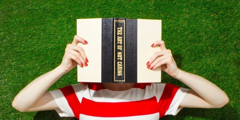 una ragazza con un libro davanti al viso