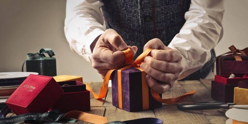 delle mani fanno il fiocco su un pacchetto