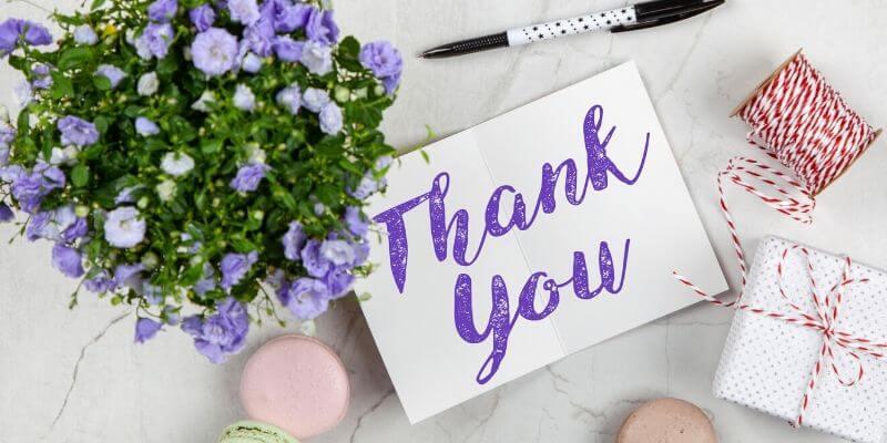 un biglietto con scritto thank you su un tavolo con un pacchetto regalo e dei macaron