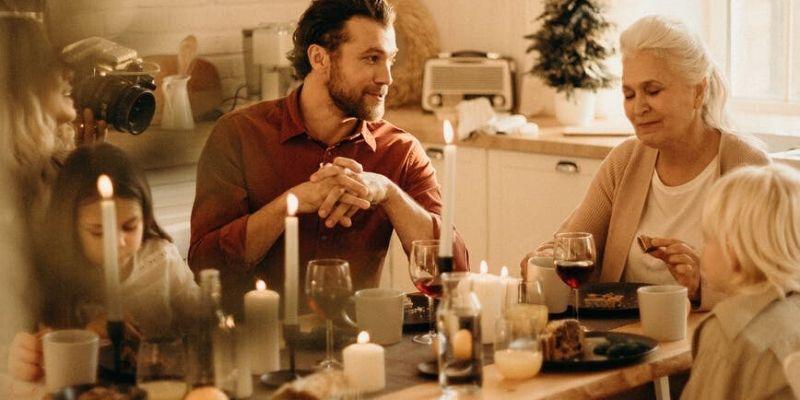 una famiglia riunita intorno a un tavolo con delle candele