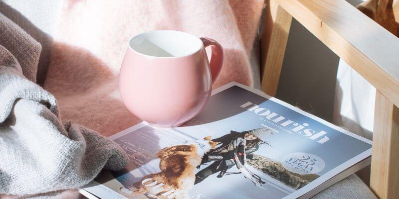 una tazza rosa e un giornale che si chiama nourish