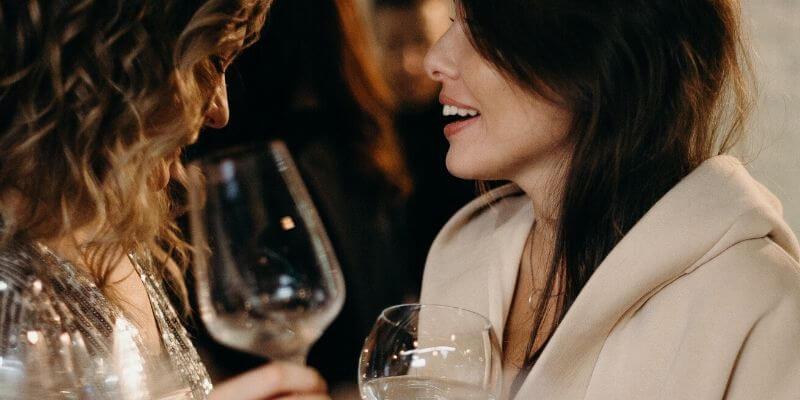 due ragazze con bicchiere di vino in mano chiacchierano