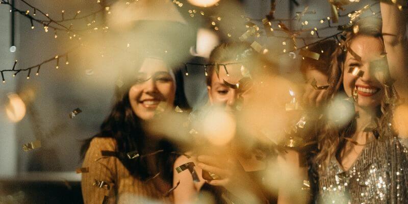 tre ragazze che ridono in mezzo a una pioggia di confetti dorati