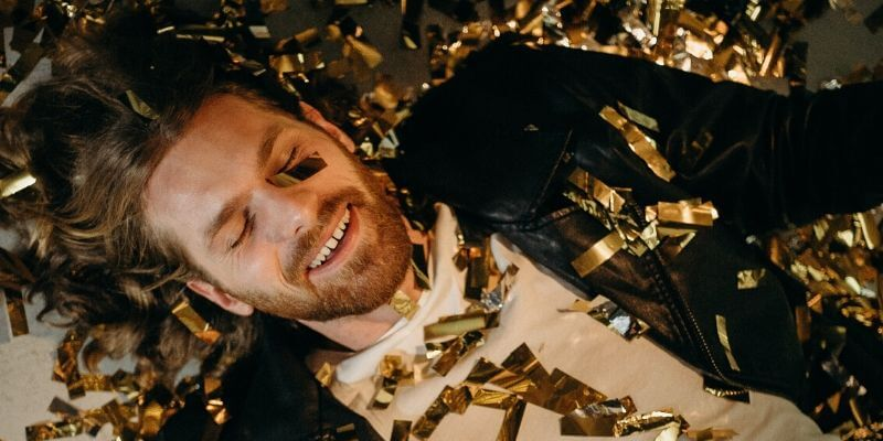 Un ragazzo sdraiato sul pavimento con addosso dei confetti color oro