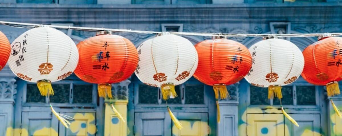 delle lanterne bianche e rosse sullo sfondo di un palazzo azzurro
