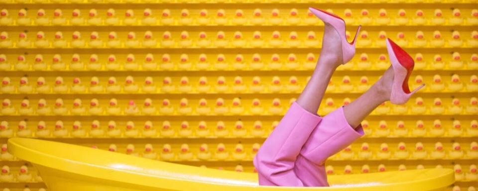 due gambe di donna con scarpe rosse emergono da una vasca da bagno