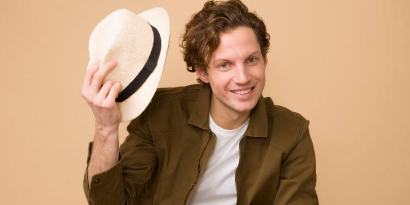 un ragazzo con un cappello in mano su sfondo beige