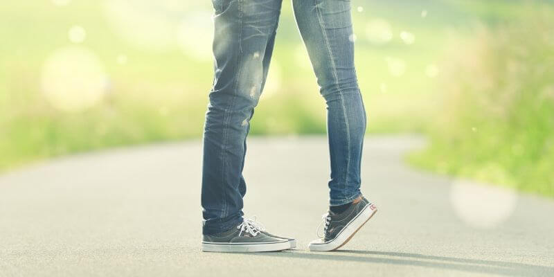 i piedi di due ragazzi in jeans e scarpe da ginnastica