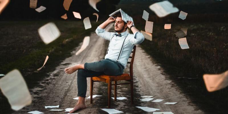 un ragazzo su una sedia con un libro sulla testa e fogli che volano intorno
