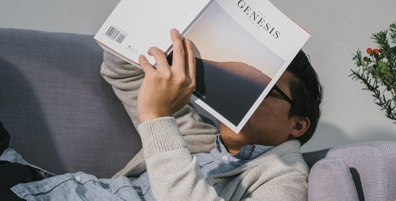 un ragazzo legge sdraiato sul divano