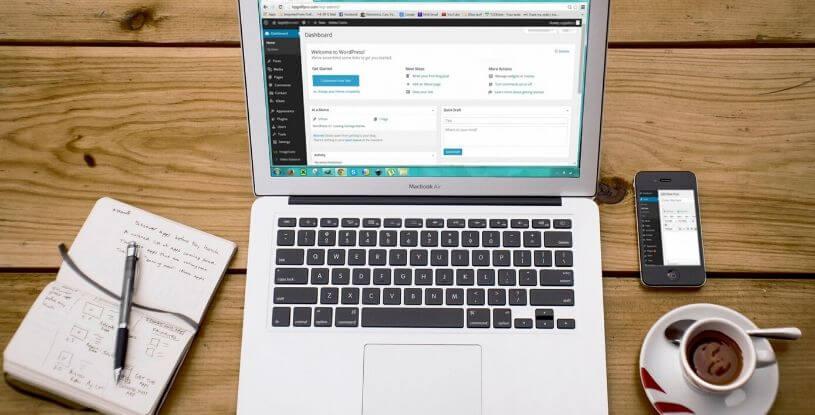 un computer su una scrivania con un bloc notes e una tazza di caffé