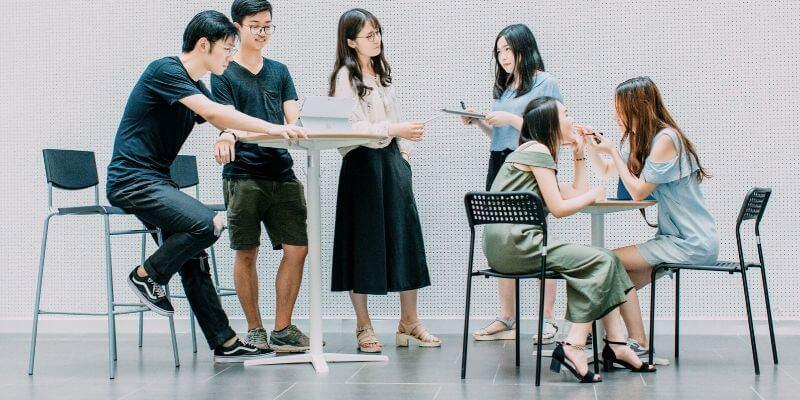 un gruppo di ragazzi asiatici seduti a dei tavolini