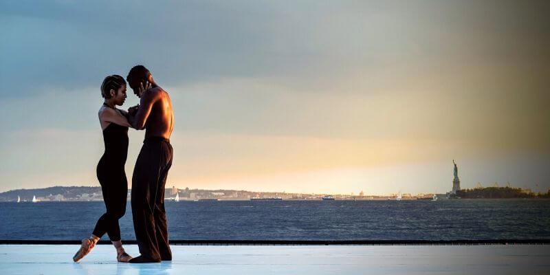 una coppia di ballerini sullo sfondo della statua della libertà
