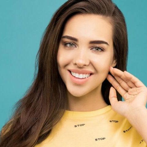 una ragazza con i capelli lunghi e una mano vicino al viso