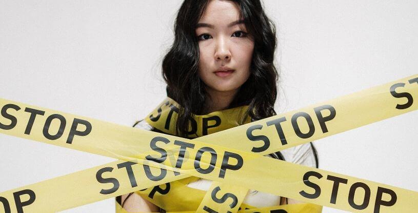 una ragazza orientale con del nastro adesivo intorno che dice STOP